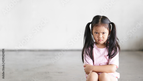 Fotografia Asian child cute touchy or kid girl sitting face frown and angry aggressive with