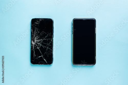 Modern touch screen smartphone with broken screen and new one on blue background Fototapete