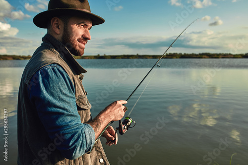 Caucasian adult bearded men stand near lake and hold fishing rod Canvas Print