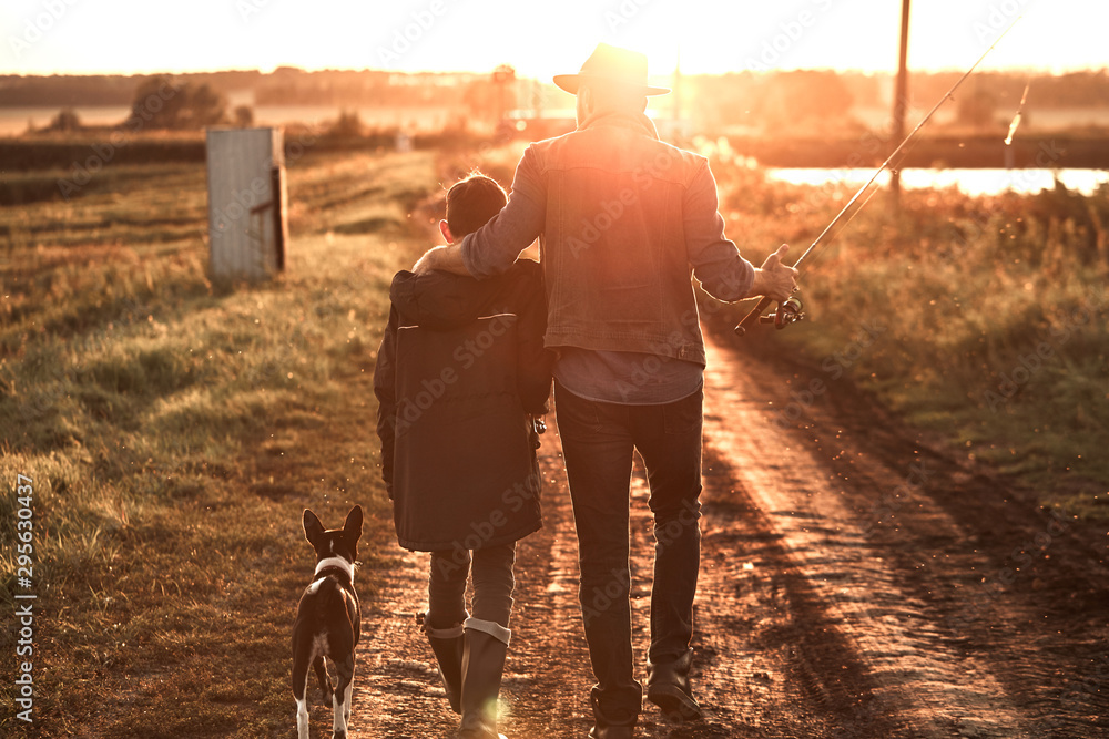 Fototapety, obrazy: Father hugged son. They and dog walk along country road along lake to fishing spot. Sunset.