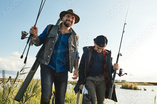 Poster Peche Happy son and father go to fishing place. They hold fishing rods, wear clothes for fishing. Sunny warm day.