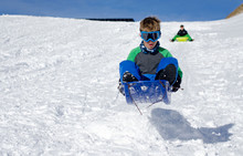 Young Boy Sledding Down A Slope And Jumping In The Snow