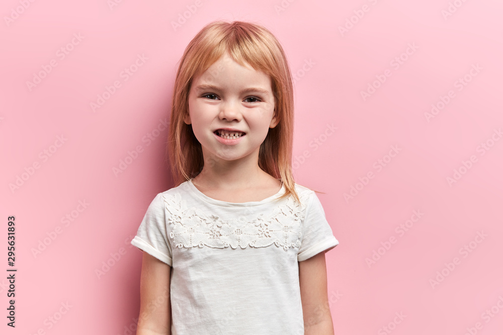 Fototapety, obrazy: Little cute angry girl clenching her teeth. close up portrait, isolated pink background, negative feeling and emotion