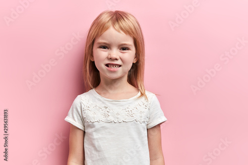 Fotografiet  Little cute angry girl clenching her teeth