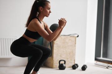 Fotografija tankog fitness modela u crnoj sportskoj odjeći izoliranoj na bijeloj pozadini