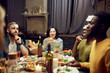 Multi-ethnic group of friends playing guessing game while sitting at table enjoying dinner party in dark room, copy space