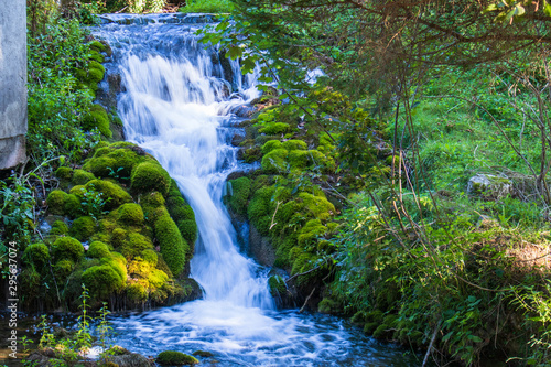 Deurstickers Bos rivier Small waterfall next to the old house in a yard in village Martin Brod in Bosnia and Herzegovina