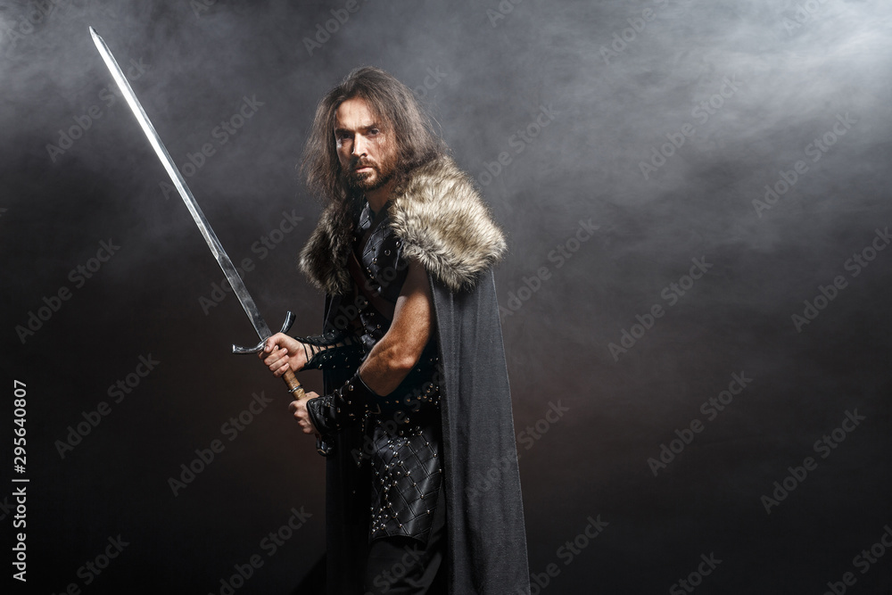 Fototapeta Man dressed in medieval armor and raincoat with longs word over smoke background. Courage fantasy warrior knight with long hair concept historical photo