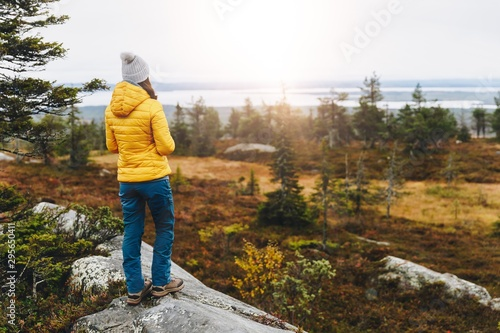 Foto auf Gartenposter Weiß Woman traveler in yellow jacket from back hike in autumn forest in Finland Lapland.