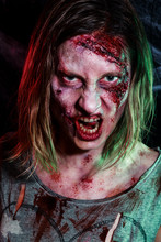Close-up Portrait Of Horrible Zombie Woman With Wounds. Horror. Halloween Make-up And Costume