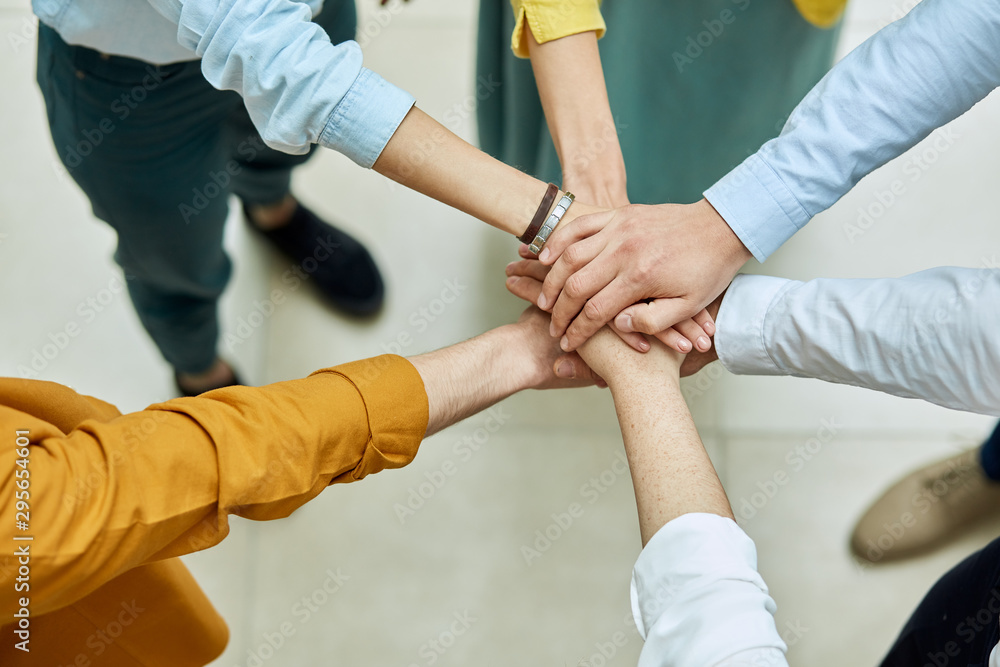 Fototapeta Friends keep hands together in sign of friendship and unity, shot from above, background of light coloured floor, people peace concept