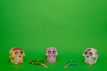 Three Skulls Of Different Colors Of The Dia De Los Muertos, Mexican Symbol Of Day Of The Dead, Next To Two Wooden Rosaries, On A Uniform Green Studio Background
