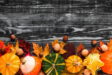 Festive Autumn Composition With Pumpkins, Nuts And Leaves On Black Wooden Background