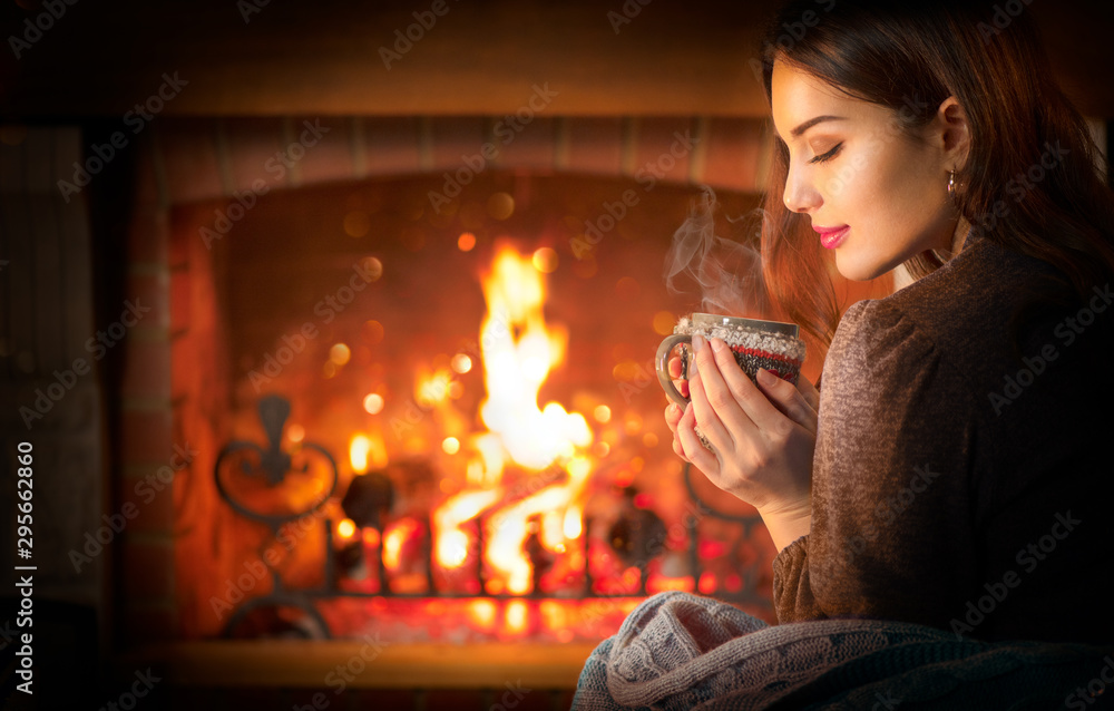 Fototapety, obrazy: Beauty young Christmas woman sitting near fireplace in dark room at home and drinking hot beverage from a big cup. Beauty girl Enjoying tea, coffee or hot chocolate in a cozy room. Xmas scene
