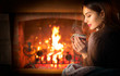 Beauty young Christmas woman sitting near fireplace in dark room at home and drinking hot beverage from a big cup. Beauty girl Enjoying tea, coffee or hot chocolate in a cozy room. Xmas scene