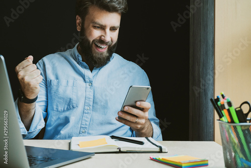 Pinturas sobre lienzo  Man rejoices in victory while looking at screen of smartphone