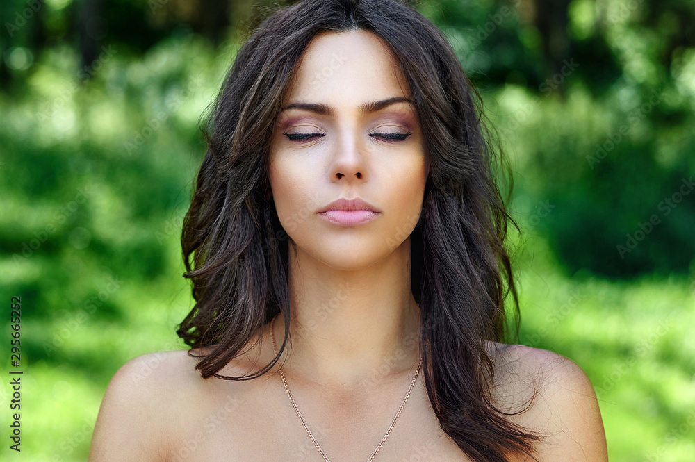 Fototapeta Beautiful woman face with perfect skin and eyes closed. Close up portrait on nature background