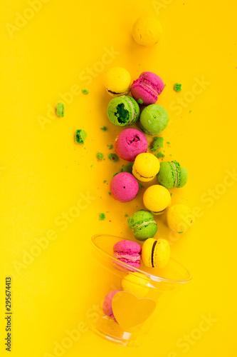 Fototapeta Colored, bright, sweet macaroons on a yellow background. Antigravity. Asymmetry. obraz
