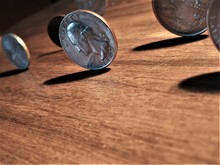 Close-up Of Several U.S. Coins Standing On End, On A Wood Surface, Casting Shadows