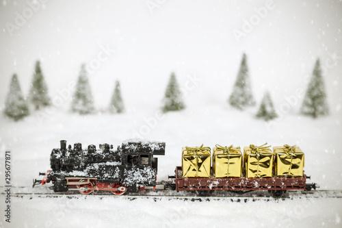 Obraz Goldene Geschenke auf einem Modellbauzug in einer Winterlandschaft - fototapety do salonu