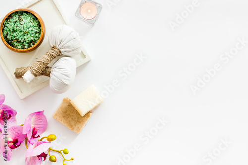 Preparing for massage in spa salon - with candles and orchids - white background top view frame copy space