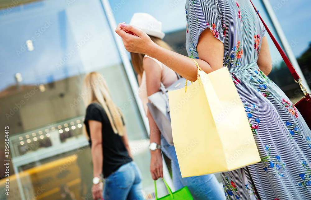 Fototapety, obrazy: Women friends with shopping bags having fun while shopping in a mall