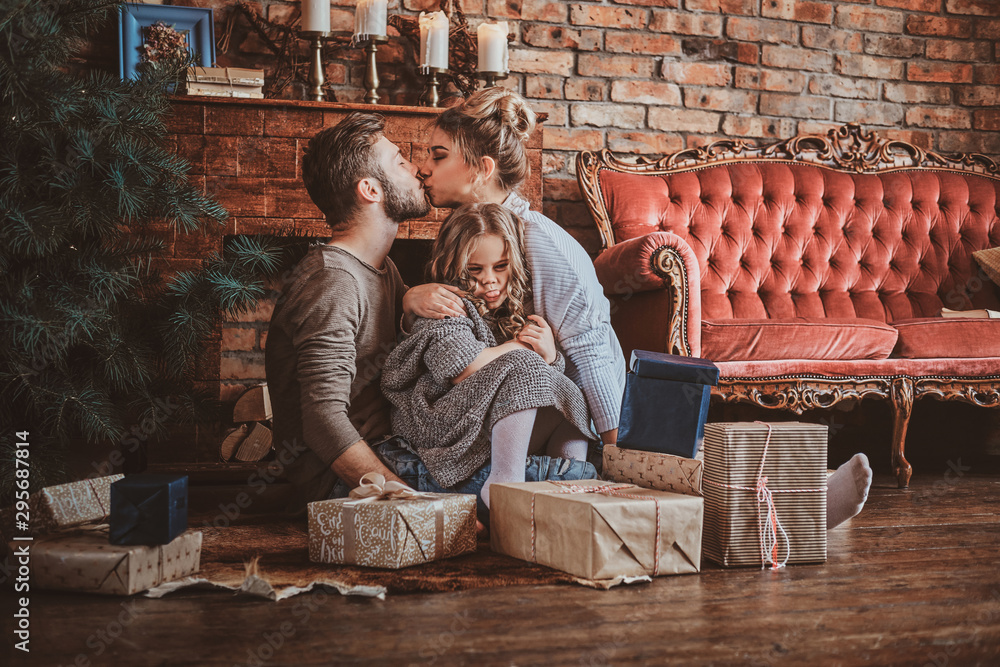 Fototapety, obrazy: Surrounded by christmas gifts, mother and father are kissing, while holding their little daughter.