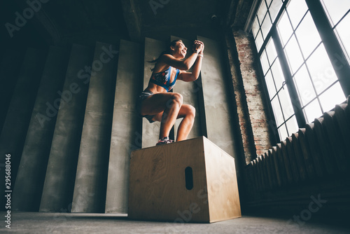 Photo  Fitness woman jumping on box while training at the gym,girl doing cross fit exercise