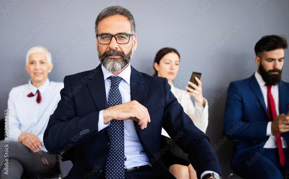Fototapeta Group of friendly businesspeople with male leader in front