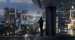 Businessman standing using smart phone in modern space watching city night view.Business with ambition and vision concept.