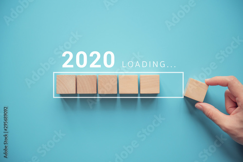 Fototapeta Loading new year 2020 with hand putting wood cube in progress bar. obraz