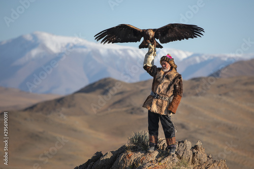 Fotografie, Obraz  Old traditional kazakh eagle hunter posing with his golden eagle in the mountains