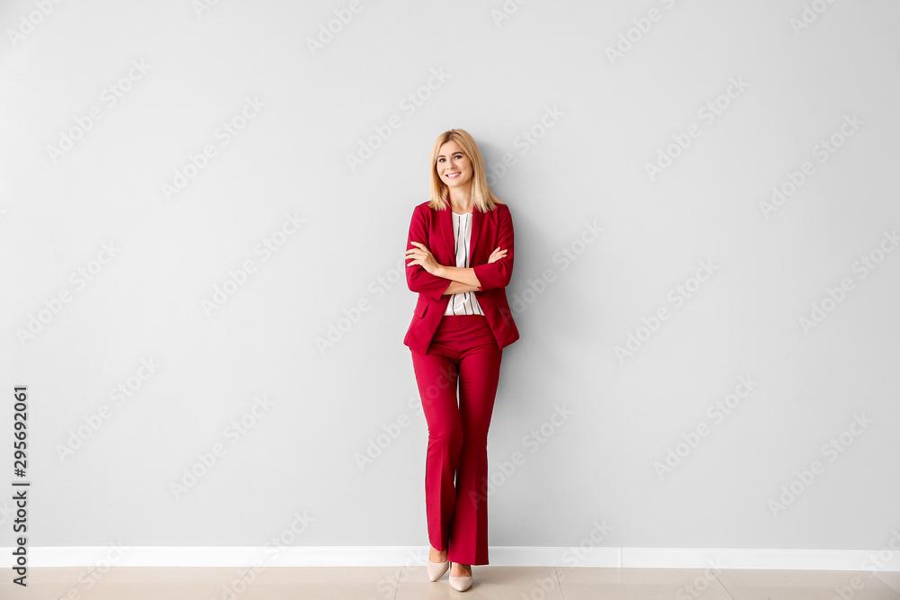 Fototapety, obrazy: Beautiful stylish businesswoman near light wall