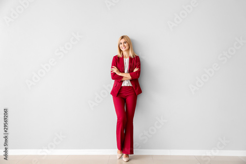 Beautiful stylish businesswoman near light wall