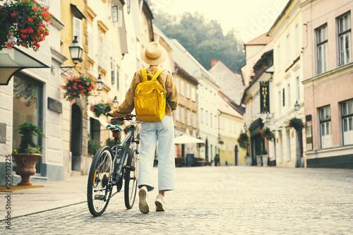 Girl with backpack and bicycle explores Ljubljana Fotobehang