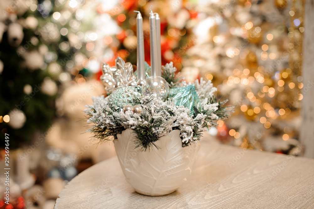 Fototapeta White vase with christmas decor composition of flowers and silver candles