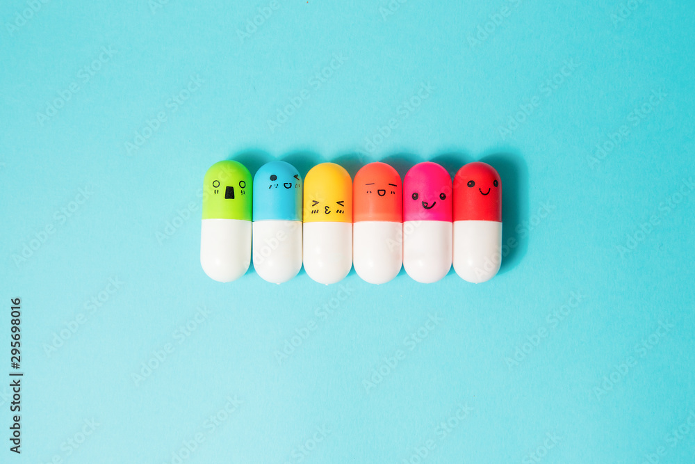 Fototapeta Bright colored pills on blue background