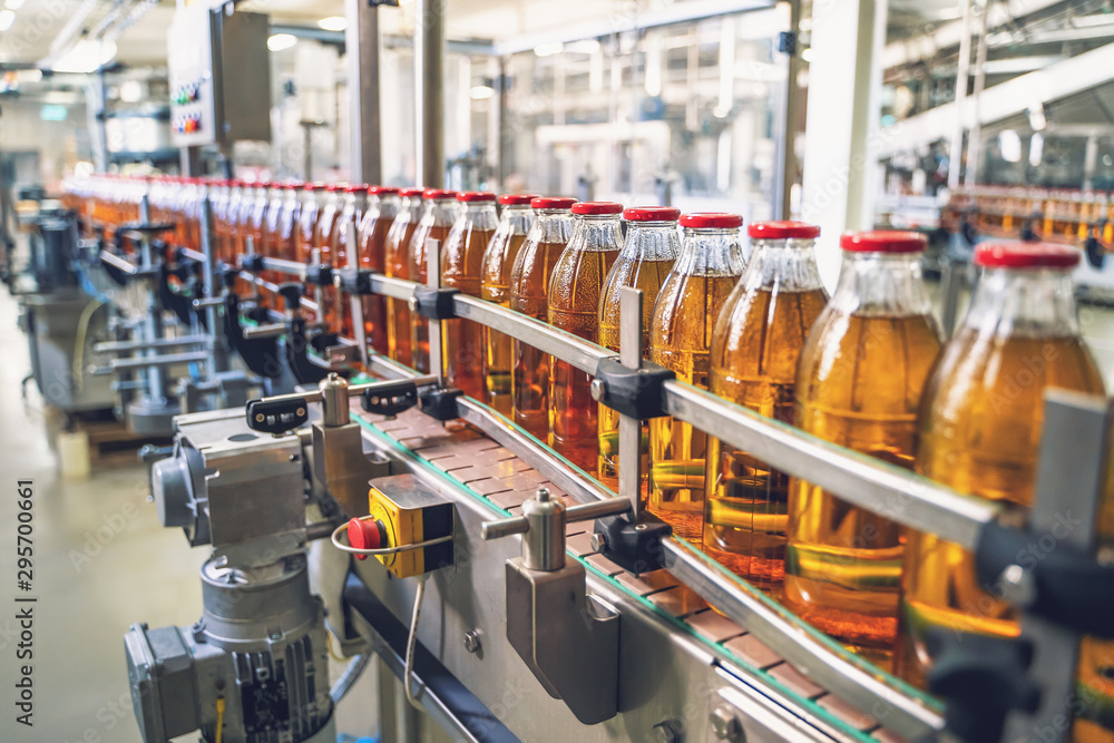 Obraz Conveyor belt, juice in glass bottles on beverage plant or factory interior, industrial manufacturing production line fototapeta, plakat
