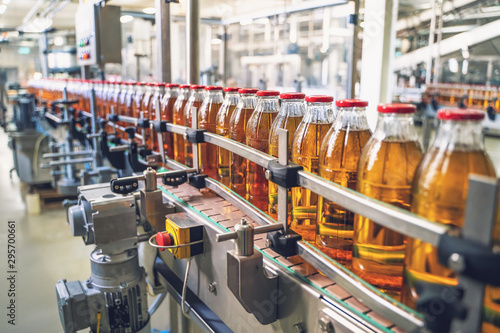 Canvastavla Conveyor belt, juice in glass bottles on beverage plant or factory interior, ind