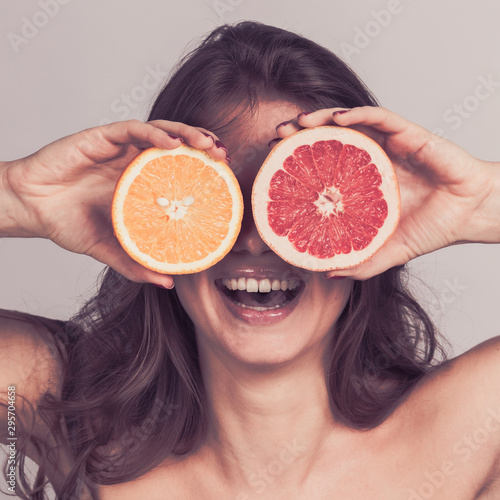 Woman holding halves of citrus fruits - 295704658