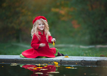A Little Blonde Girl In A Red Coat And Beret Throws Leaves Into The Water. Girl Sitting By The Water. Autumn Photography.