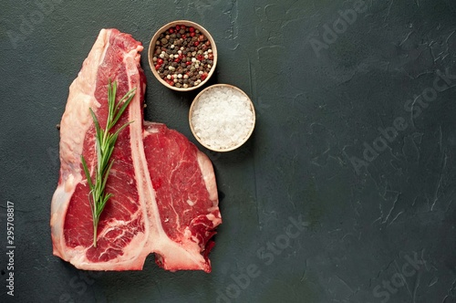 Poster Amsterdam Raw t-bone steak with fresh herbs on a concrete or slate background, top view, place for text,