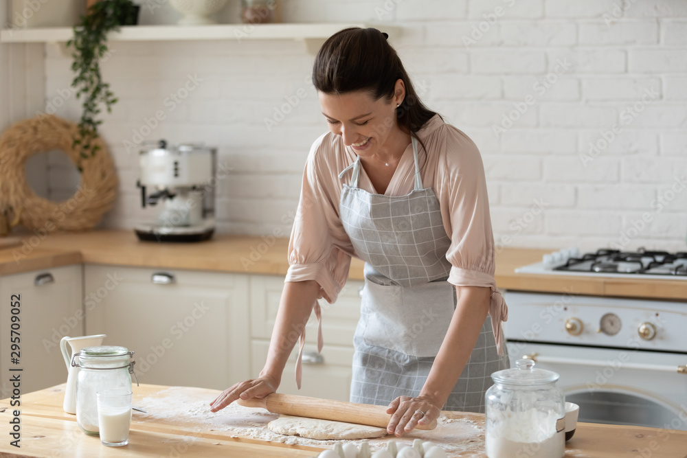 Fototapeta Smiling young woman wearing apron rolling out dough in kitchen
