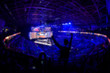 canvas print picture - Blurred background of an esports event - Fan on a tribune at tournament's arena with hands raised.