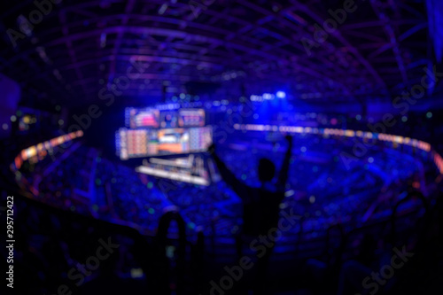 Cuadros en Lienzo  Blurred background of an esports event - Fan on a tribune at tournament's arena with hands raised