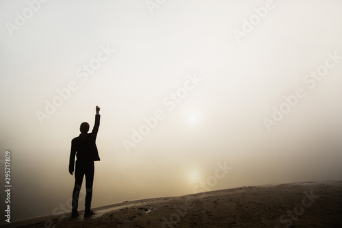 Photo Stands Roe Business success. Silhouette of happy businessman on fog background. Successful man raise hand against dawn. Man silhouette in costume. Business concept with ree copyspace. Life success. Win contest
