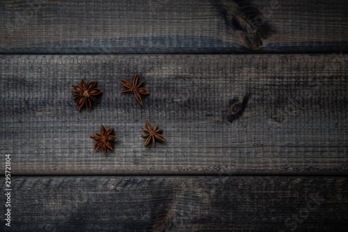 Vászonkép  Anise stars on a dark wooden table
