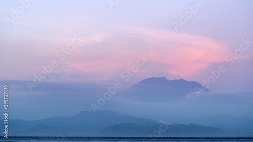 Poster Rose clair / pale Sun sets over the mist of the volcano Agung in Bali, Indonesia