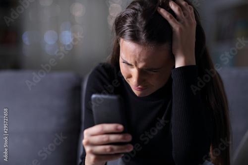 Obraz na płótnie Sad girl checking bad news on mobile phone in the dark