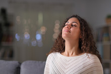 Relaxed Woman Breathing Fresh Air In The Night At Home